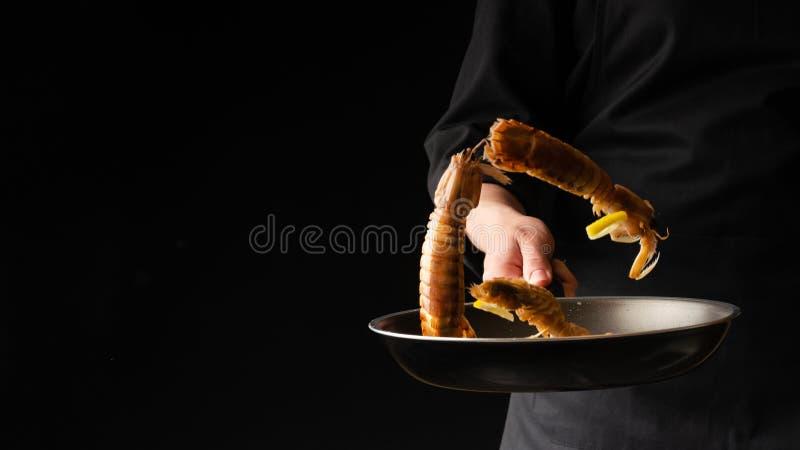 Il cuoco unico prepara i frutti di mare, gamberetto di mantide, cucina asiatica orientale, dilikates, su un fondo nero, foto oriz fotografia stock libera da diritti