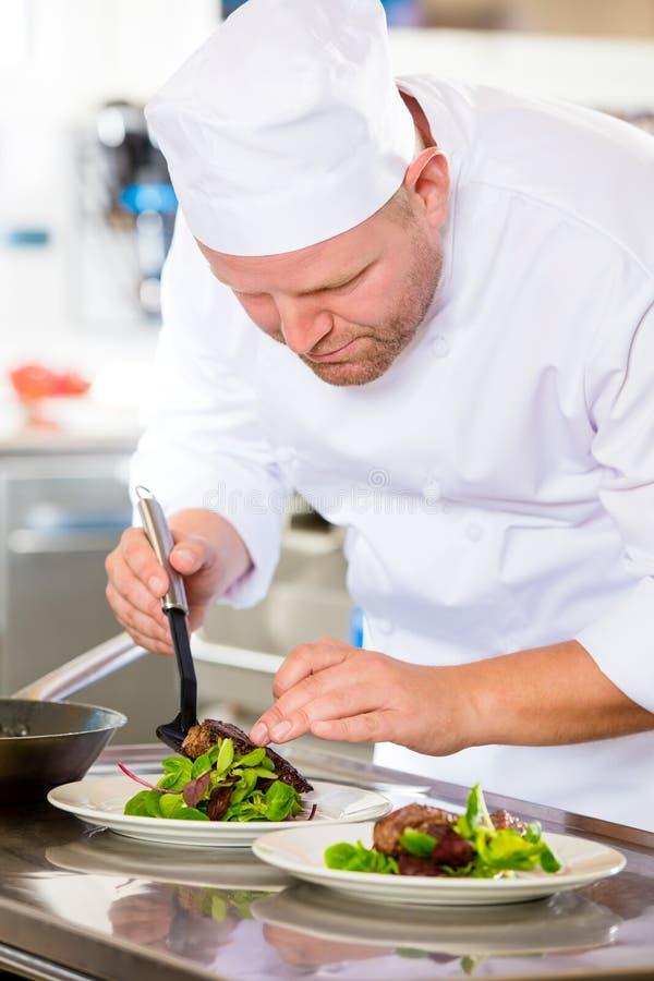 Il cuoco unico prepara il piatto della bistecca al ristorante gastronomico fotografie stock libere da diritti