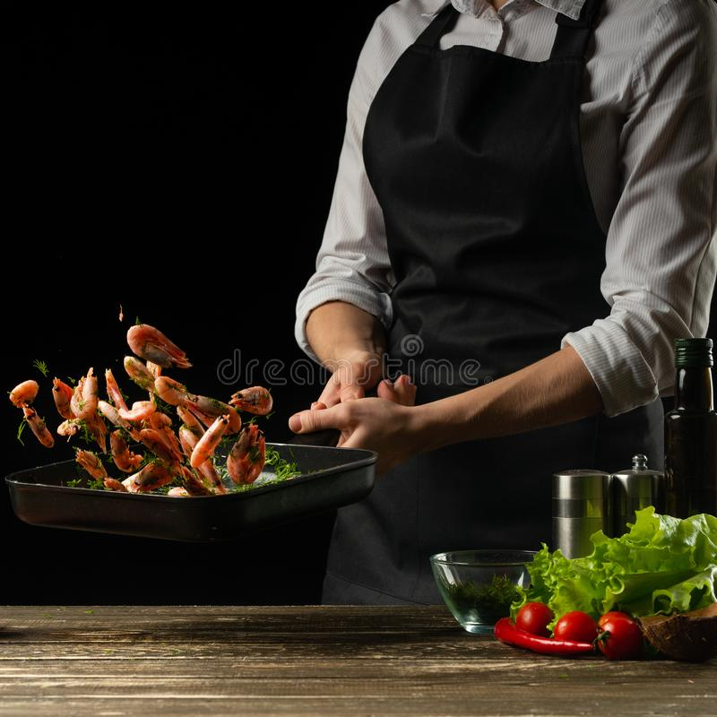 Il cuoco unico professionista prepara un'insalata di gamberetto fresco e delle verdure su un fondo scuro, congelantesi nel moto F fotografie stock