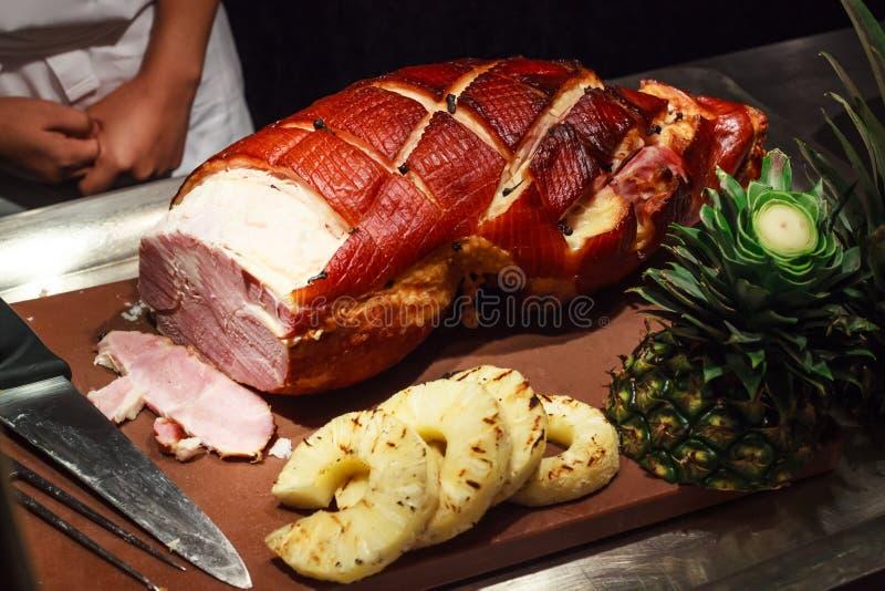 Il cuoco unico pronto ad affettare il miele lustrato ha arrostito la carne di maiale per gli ospiti in vacanza, evento del prosci fotografia stock