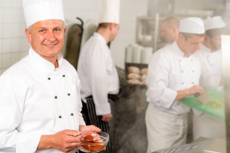 Il cuoco unico sorridente della cucina professionale aggiunge l'alimento della spezia fotografia stock libera da diritti