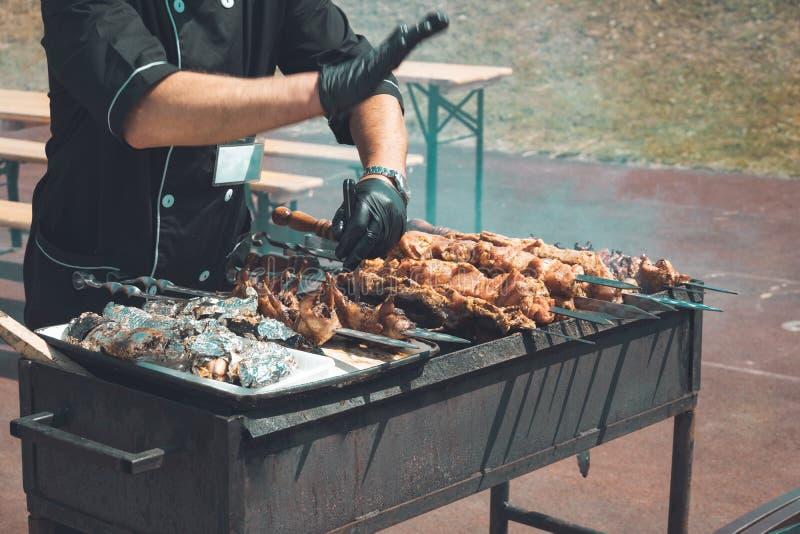 Il cuoco unico sta cucinando la carne arrostita all'aperto sugli spiedi, kebab, quaglie dello shashlik, verdure, su un addetto al fotografie stock