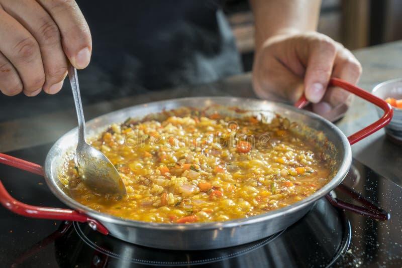 Il cuoco unico sta cucinando la paella con il cucchiaio, fine su immagini stock