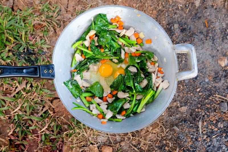 Il cuoco unico tailandese che cucina le scalpore ha fritto la verdura, la carne di maiale e l'uovo fotografia stock libera da diritti