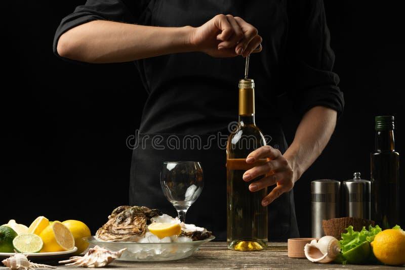 Il cuoco unico versa, assaggia il vino asciutto italiano dell'ostrica con il limone fotografia stock libera da diritti