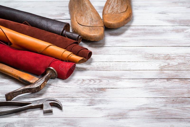 Il cuoio brillantemente colorato in rotoli, attrezzi e scarpa dura su fondo di legno bianco Mestiere di cuoio Copi lo spazio immagini stock libere da diritti