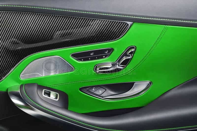 Il cuoio verde dell'automobile ed i dettagli interni del carbonio della maniglia di porta con le finestre alimentano i comandi e  fotografia stock