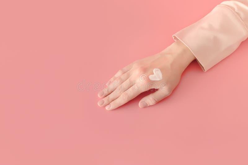 Il cuore applicato della donna ha modellato la sbavatura di lozione crema a disposizione Auto--l fotografie stock