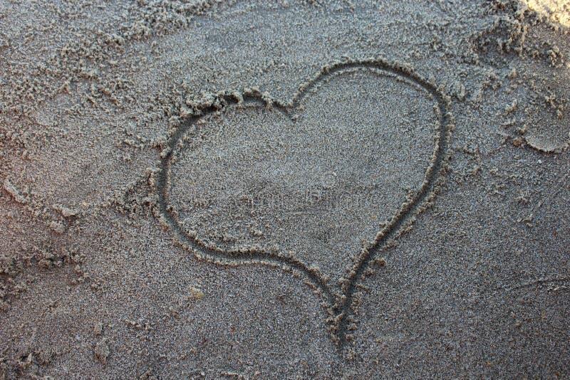 Il cuore assorbe la sabbia della spiaggia fotografie stock