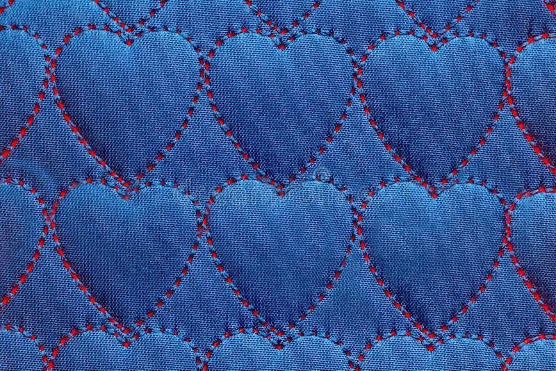 Il cuore astratto del fondo sui tessuti, fili rossi ha cucito i punti sotto forma dei cuori su cotone blu, denim fotografie stock