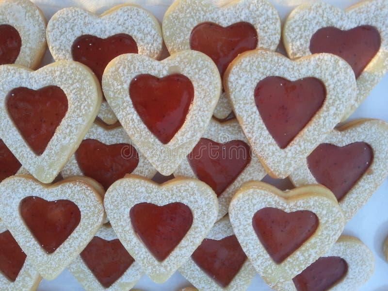 Il cuore bianco rosso ha modellato i biscotti allineati sopra a vicenda fondo bianco immagine stock libera da diritti