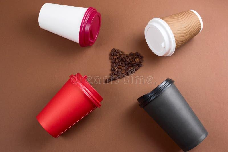 il cuore dei chicchi di caffè e le varie bevande del caffè in tazze eliminabili di carta pianamente pongono il fondo marrone, der fotografia stock