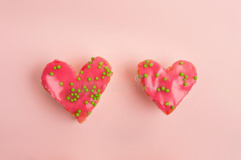 Il cuore del biglietto di S. Valentino ha modellato i dolci della fragola decorati con le palle verdi dello zucchero su fondo ros fotografia stock libera da diritti