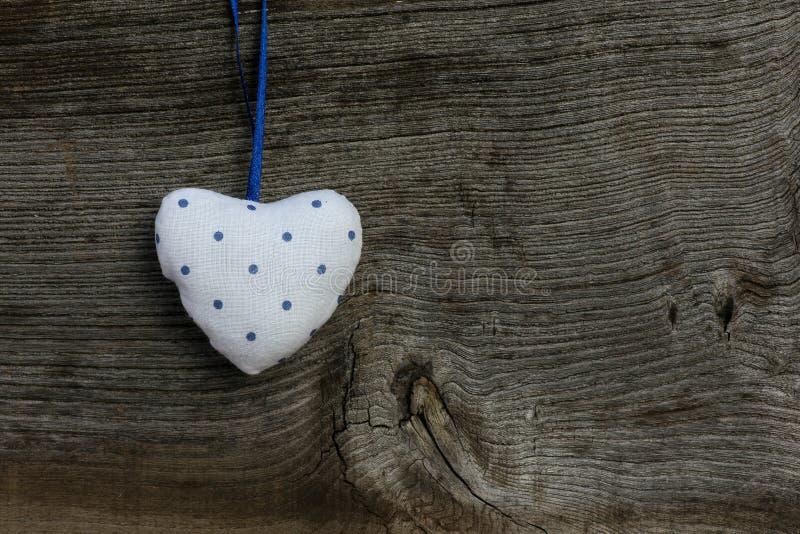 Il cuore del modello del biglietto di S. Valentino blu bianco di amore che appende sul testo di legno fotografie stock