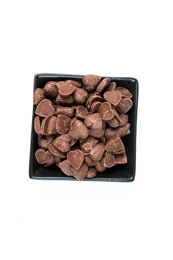 Il cuore della caramella di Brown ha modellato i pezzi del chip del cioccolato al latte fotografia stock