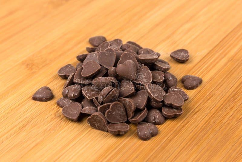 Il cuore della caramella di Brown ha modellato i pezzi del chip del cioccolato al latte immagini stock