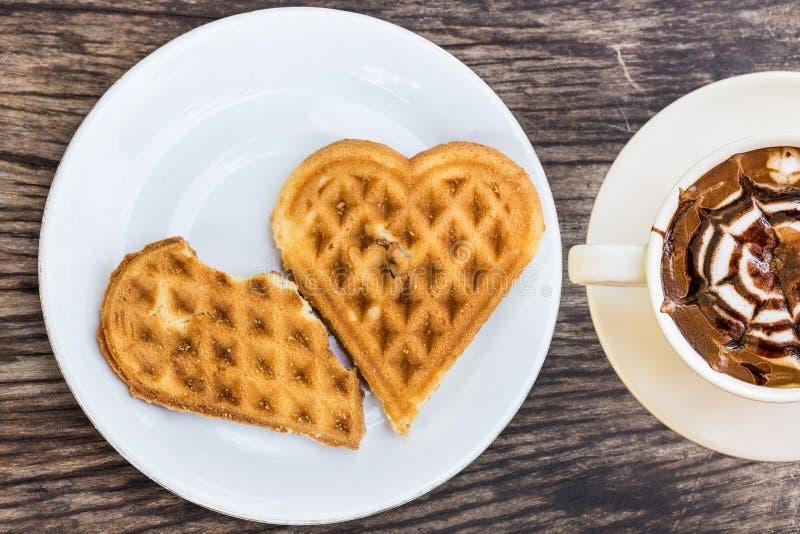 Il cuore delle cialde ha modellato sulla tazza bianca di caffè e del piatto immagine stock