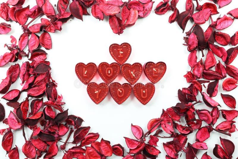 Il cuore di San Valentino fatto del telaio delle rose rosse con cuore ha modellato ti amo le candele su fondo bianco isolato fotografia stock