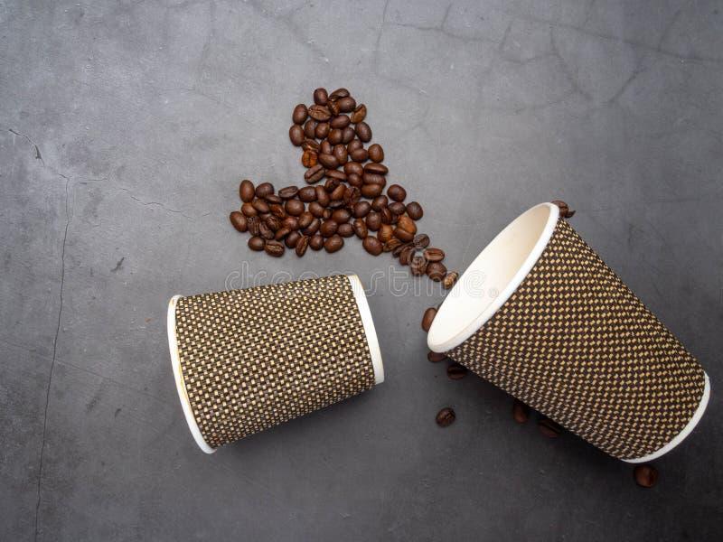 il cuore di vista superiore dei chicchi di caff? e le tazze eliminabili di carta pianamente pongono il fondo concreto, falso sull fotografie stock