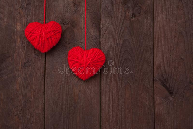 Il cuore due ha fatto del filato di lana rosso su fondo di legno Concetto di giorno del ` s del biglietto di S fotografia stock libera da diritti