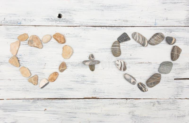 Il cuore due ha modellato le pietre del ciottolo su un vecchio legno immagini stock libere da diritti