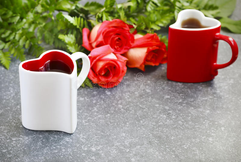 Il cuore due ha modellato le tazze con tè ed il mazzo delle rose immagine stock libera da diritti