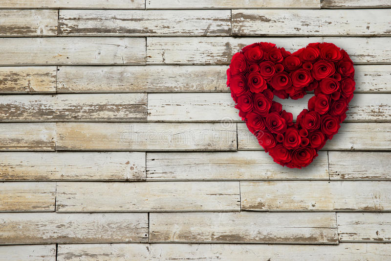 Il cuore fatto di rosso di legno delle rose ha dipinto pendere da una parete di legno fotografia stock libera da diritti