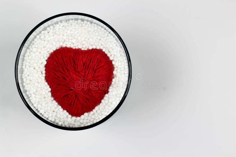 Il cuore ha fatto del filato di lana, protettivo dalle palline in espansione del polistirolo fotografia stock libera da diritti