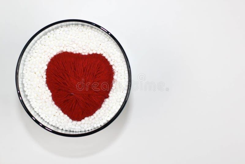 Il cuore ha fatto del filato di lana, protettivo dalle palline in espansione del polistirolo fotografie stock libere da diritti