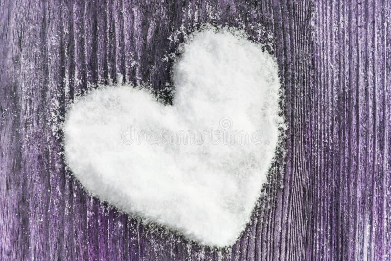 Il cuore ha fatto di neve su un fondo di legno immagine stock libera da diritti
