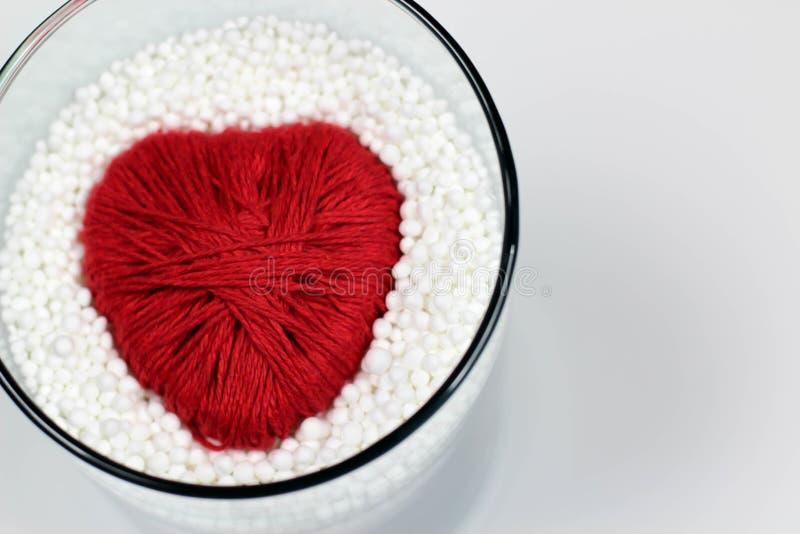 Il cuore ha fatto il filato di lana, protettivo dalle palline in espansione del polistirolo fotografia stock libera da diritti