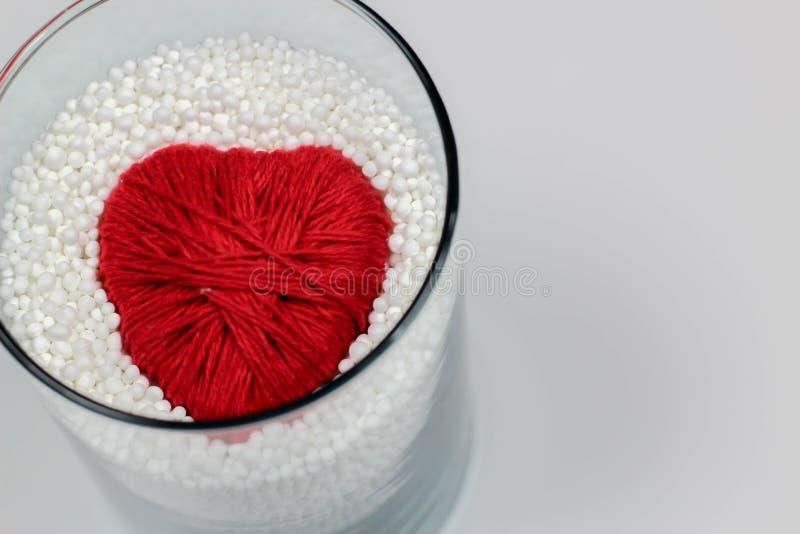 Il cuore ha fatto il filato di lana, protettivo dalle palline in espansione del polistirolo fotografie stock libere da diritti