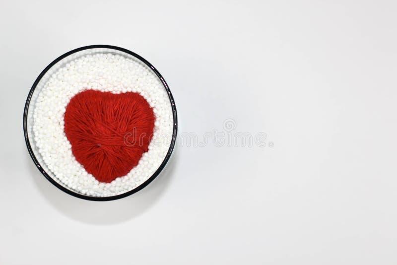 Il cuore ha fatto il filato di lana, protettivo dalle palline in espansione del polistirolo immagini stock