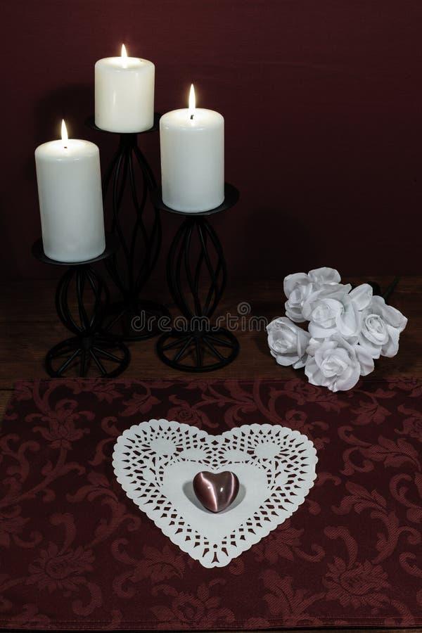Il cuore ha modellato il dollie e pietra preziosa, tre candele bianche nei supporti del metallo e mazzo delle rose bianche sulla  immagini stock libere da diritti