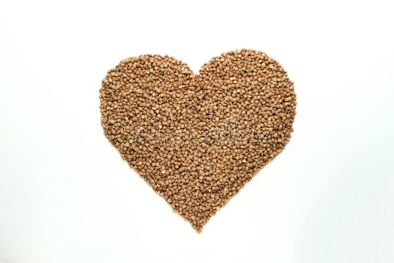 Il cuore ha modellato il grano saraceno su fondo bianco fotografia stock