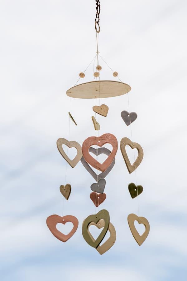 Il cuore ha modellato il cellulare ceramico del vento che appende con il cielo blu defocused immagini stock