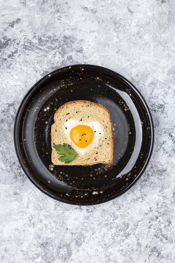 Il cuore ha modellato l'uovo cucinato su una fetta di pane tostato fotografie stock libere da diritti