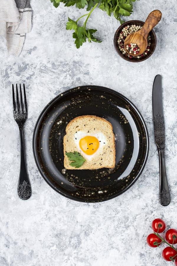 Il cuore ha modellato l'uovo cucinato su una fetta di pane tostato immagine stock