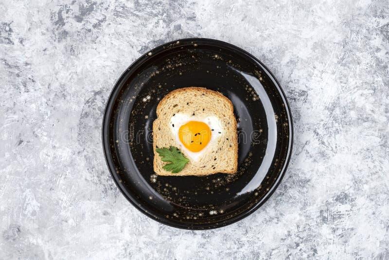 Il cuore ha modellato l'uovo cucinato su una fetta di pane tostato fotografie stock