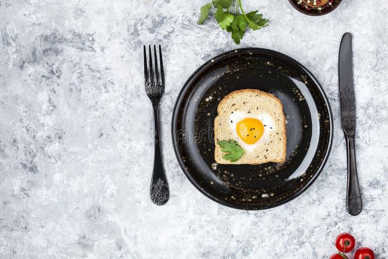 Il cuore ha modellato l'uovo cucinato su una fetta di pane tostato immagini stock libere da diritti