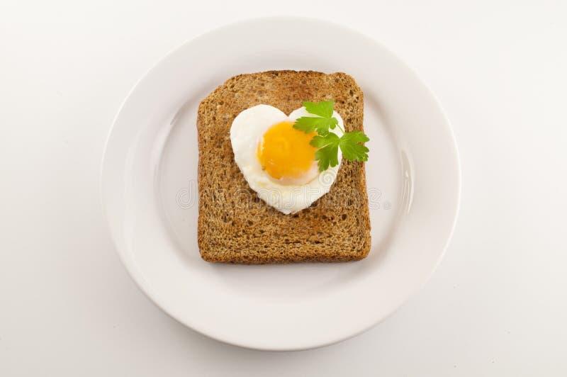 Il cuore ha modellato l'uovo su una parte di pane tostato immagini stock