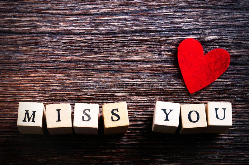 Il cuore ha modellato la masticazione delle caramelle e le parole vi mancano sui cubi, fondo di legno Spazio libero per il vostro fotografia stock