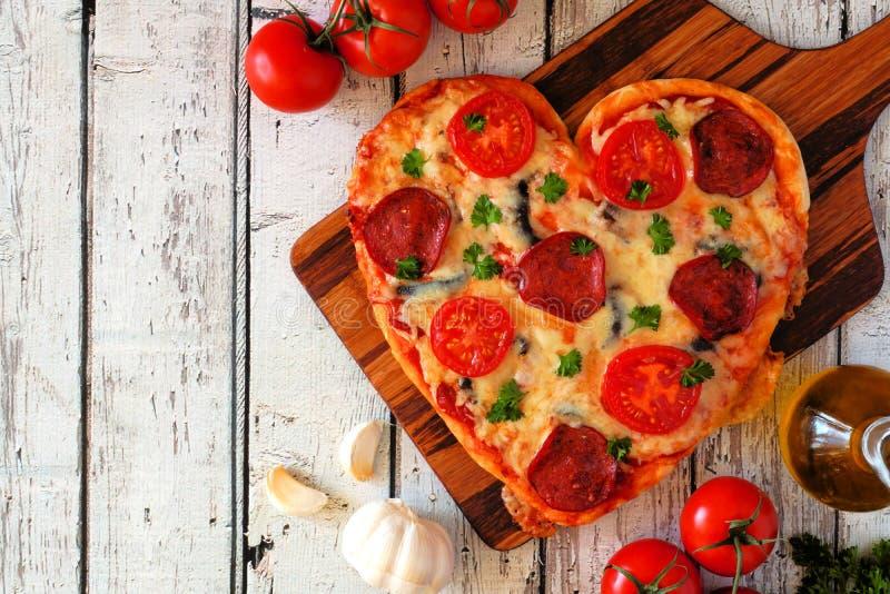 Il cuore ha modellato la pizza per il giorno di biglietti di S. Valentino sopra legno bianco, sopra la vista, scena laterale dell fotografia stock