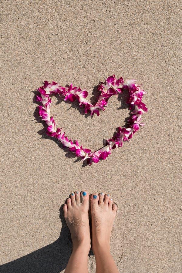 Il cuore ha modellato la spiaggia bianca della sabbia di mare della ghirlanda del fiore dell'orchidea con i piedi della donna fotografia stock