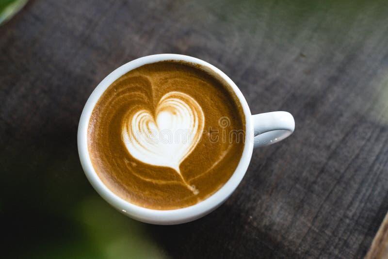 Il cuore ha modellato il latte del caffè sulla tavola di legno fotografia stock