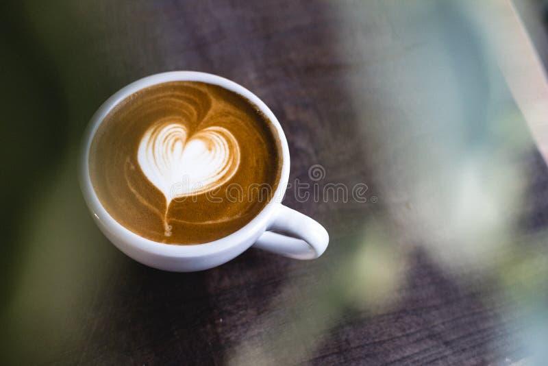 Il cuore ha modellato il latte del caffè sulla tavola di legno fotografie stock