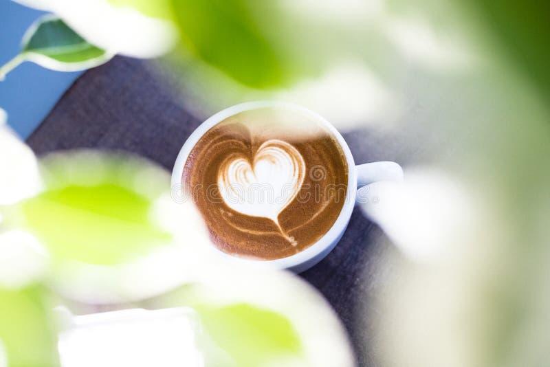 Il cuore ha modellato il latte del caffè sulla tavola di legno immagine stock libera da diritti