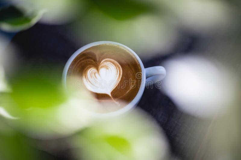Il cuore ha modellato il latte del caffè sulla tavola di legno immagini stock