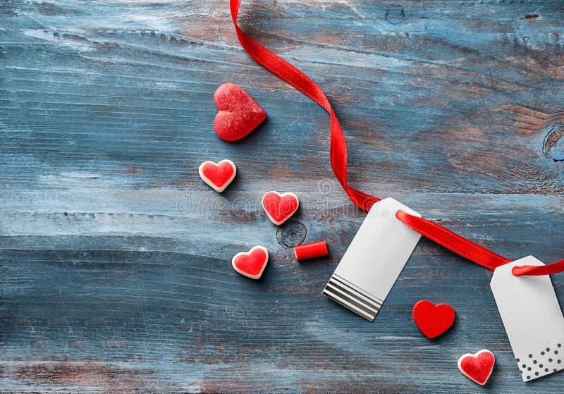Il cuore ha modellato le caramelle della gelatina con il nastro rosso e le etichette sul fondo di legno di colore fotografie stock libere da diritti