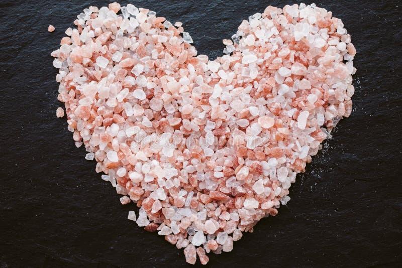 Il cuore ha modellato il sale himalayano a bordo di fondo Vista superiore fotografie stock libere da diritti